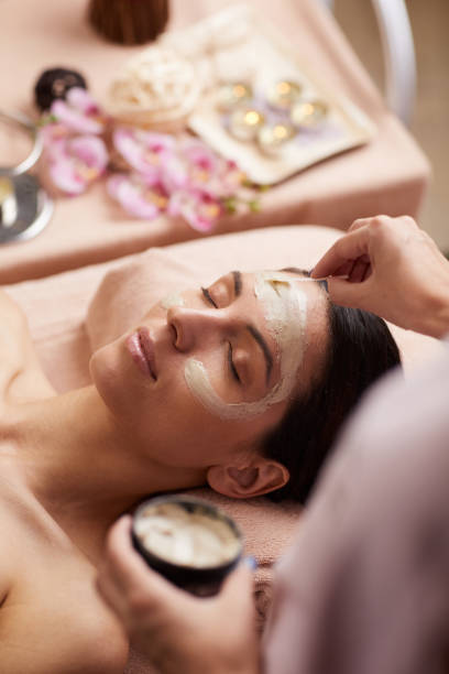 Beautician using cosmetic spatula while applying facial mask to client during beauty treatment stock photo