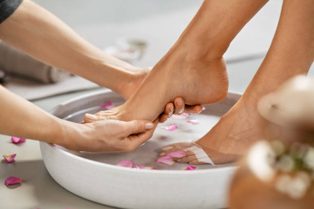Beautician washing woman feet for pedicure treatment stock photo