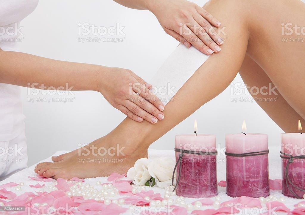 Beautician Waxing A Woman's Leg stock photo