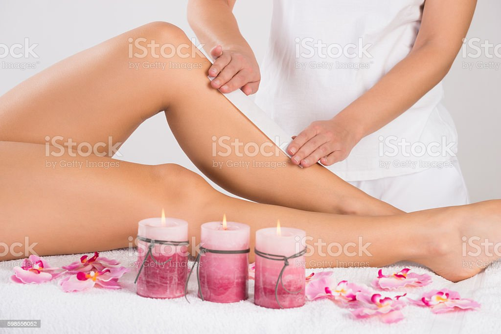 Beautician Waxing Woman's Leg At Salon stock photo