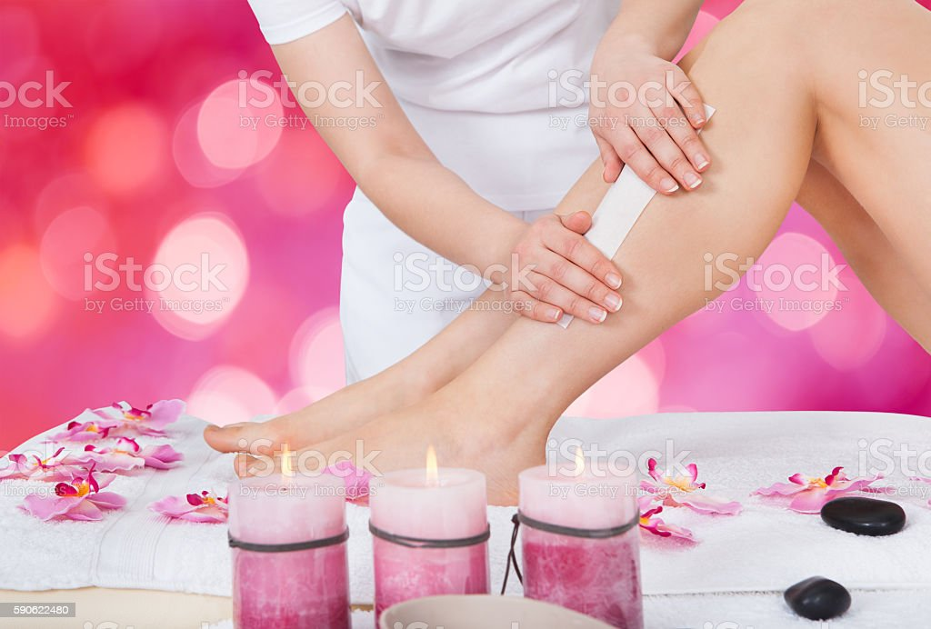 Beautician Waxing Woman's Leg In Beauty Salon stock photo
