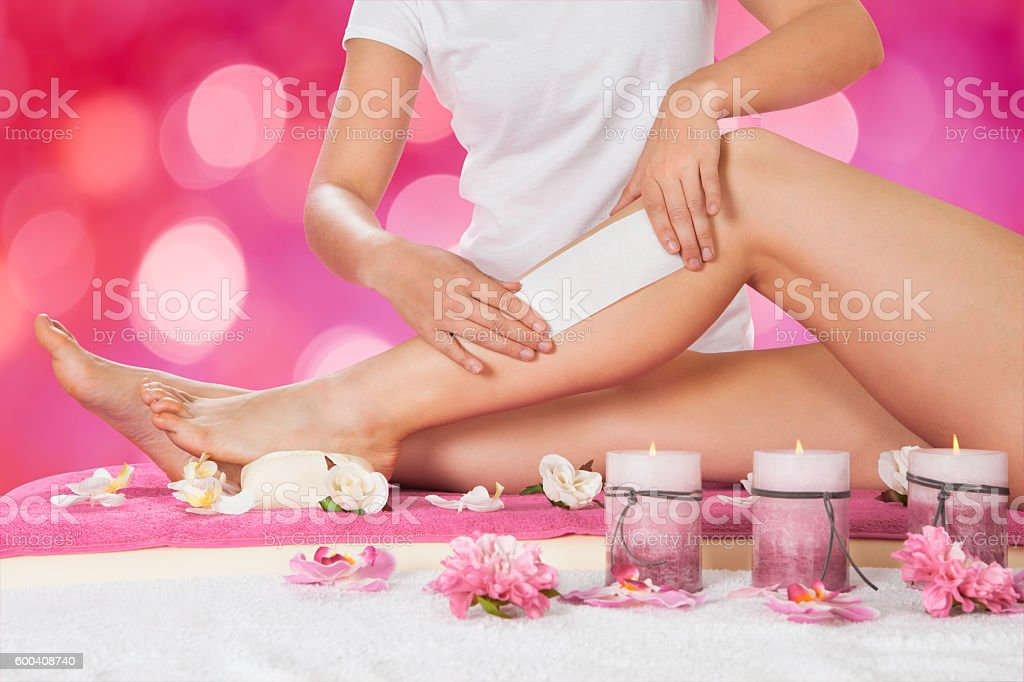 Beautician Waxing Woman's Leg In Salon stock photo