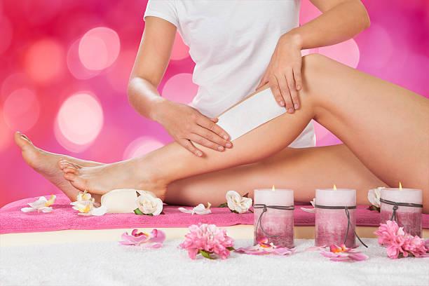 beautician waxing woman's leg in salon - wachsblume stock-fotos und bilder