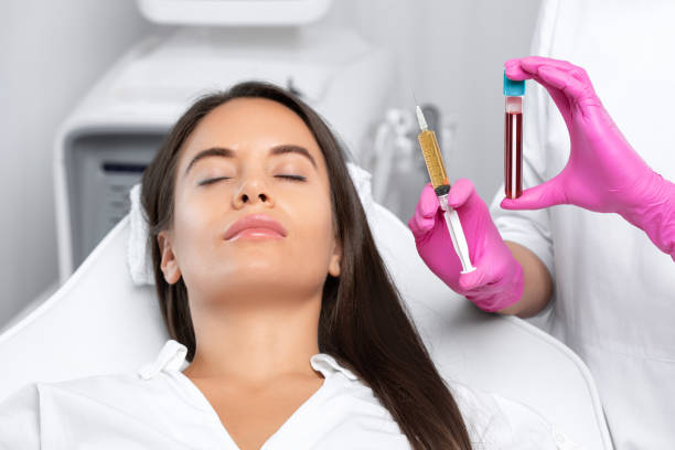 Beautician will do PRP therapy for the face against wrinkles and against hair loss of a beautiful woman in beauty salon.Doctor holds test tubes with venous blood and blood plasma.Cosmetology concept. stock photo