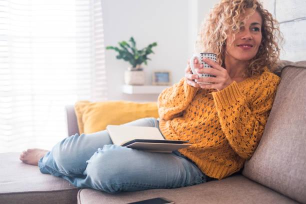 hermosa de 40 años caucásico señora siéntese en el sofá bebiendo té y leyendo un libro para la actividad de ocio interior por la tarde en casa - después de estilo de vida de trabajo para el concepto de personas - café bebida fotografías e imágenes de stock