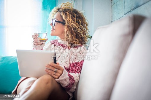 beautiful 40 years old middle age woman caucasian curly long hair at home working at tablet while look outside the window. water with lemon to have care of her body and wellness beauty. relaxed and happiness concept