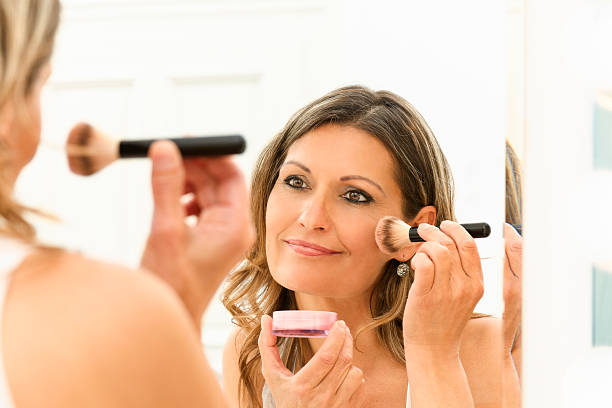 beautiful 40s woman applying makeup - 40 49 years stock pictures, royalty-free photos & images