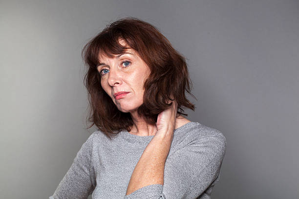 beautiful 50s woman with seasonal affective disorder syndrome disillusioned mature woman with brown hair and grey sweater thinking,looking bored and concerned affective stock pictures, royalty-free photos & images