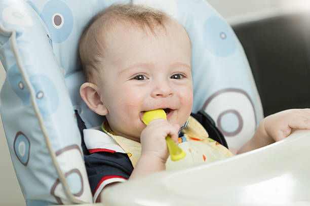 Beautiful 9 month baby boy playing with spoon while eating – Foto