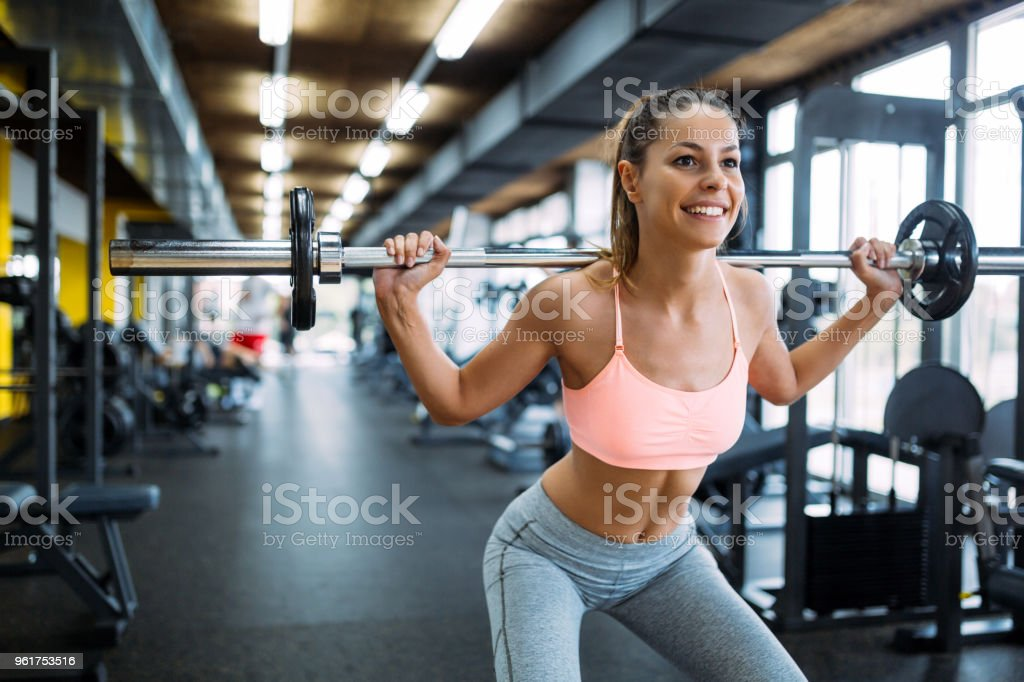 Beautiful active woman doing squats in gym stock photo