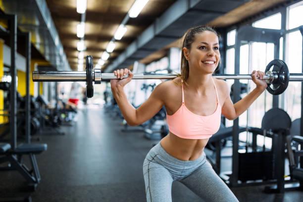 hermosa mujer activa haciendo sentadillas en el gimnasio - entrenamiento con pesas fotografías e imágenes de stock