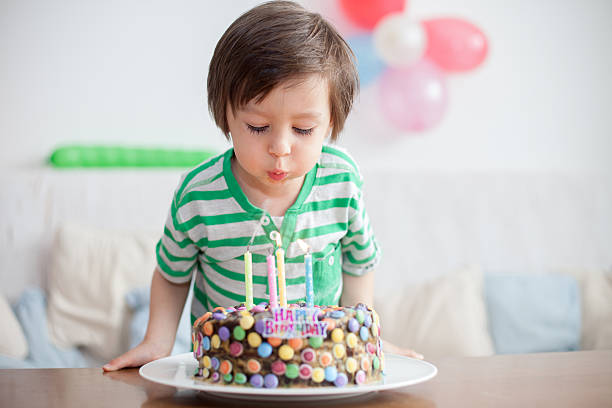 Beautiful adorable four year old boy in green shirt, celebrating stock photo