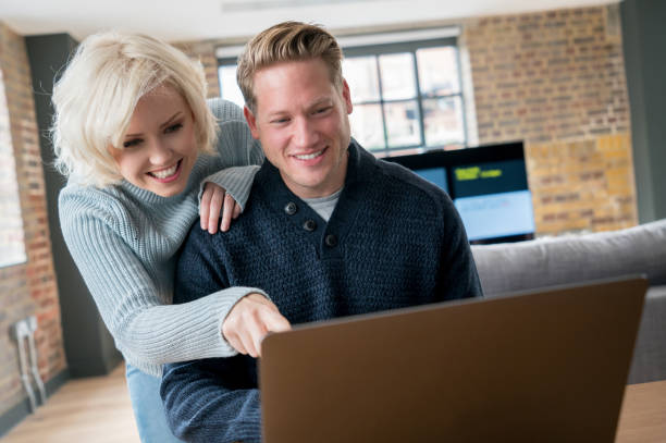 Beautiful adult couple at home and man working on his laptop while woman pointing at the screen leaning on him happy stock photo