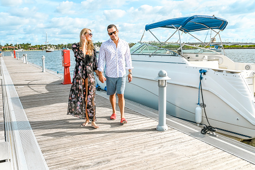 Very attractive adult couple in their 30's to 40's on a dock in Palm Beach Florida a luxury location, with idyllic ocean behind them and a small yacht, speed boat. They are happy and flirtatious with each other, they are relaxed as if on vacation. They have a high end look as if on a resort or cruise vacation