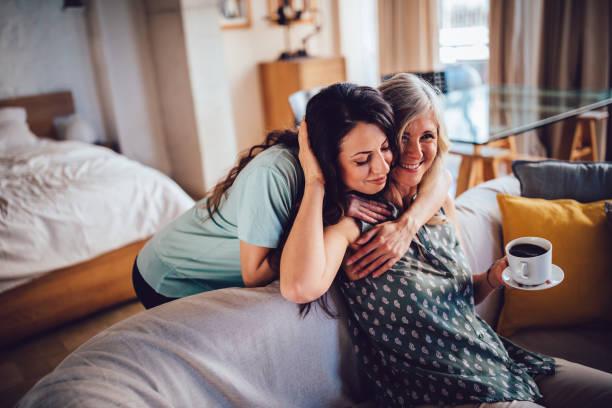 ソファーに座っていた先輩の母親を笑顔を受け入れる美しい大人の娘 - 娘 ストックフォトと画像