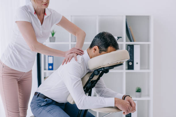 beautiful adult masseuse doing seated massage for businessman stock photo