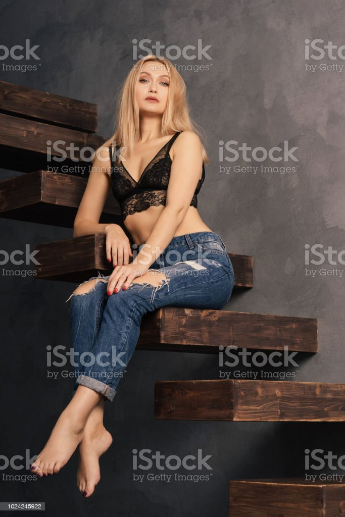 beautiful adult woman in a bra and jeans posing on a wooden cantilever stairs stock photo