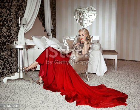 istock Beautiful adult woman in fashion red dress sitting on armchair 621373312