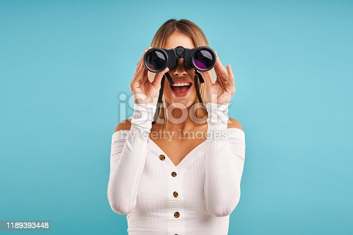 Blond beautiful adult woman posing over blue background with binoculars