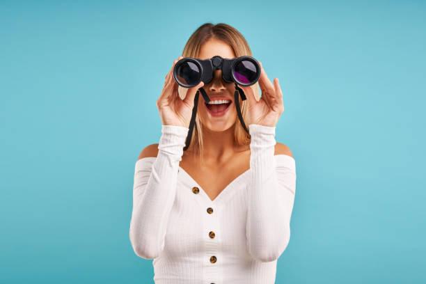 Schöne erwachsene Frau posiert über blauem Hintergrund mit Fernglas – Foto