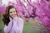 A beautiful adult woman with curly hair in a sweater on the background of the garden with cherry blossoming.