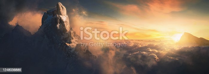 istock Beautiful aerial landscape of mountain peak at sunset above the clouds - panoramic 1248036885