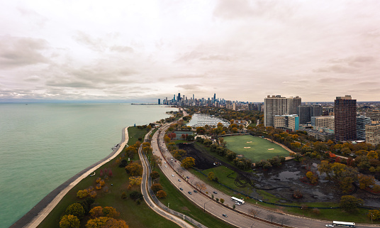 Beautiful aerial skyline view of the City of Chicago from the north side along Lincoln Park with Lake Michigan, traffic on Lake Shore drive, construction, and driving range below and cloudy sky above.