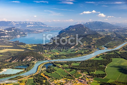 Vibrant color photography of beautiful aerial view French landscape viewed from Grand Colombier summit in middle of Bugey mountains, with Rhone river, vibrant green fields and Lake Bourget in Savoie. Shot from Grand Colombier mountain summit during a sunny summer day, in Bugey mountains, in Ain department not far from Jura and Savoie border near Culoz city, Auvergne-Rhone-Alpes region in France (Europe).