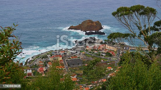 Beautiful aerial view of small fishing village Porto Moniz on the northwestern coast of Madeira island, Portugal with the popular natural swimming pools. Focus on village in center.