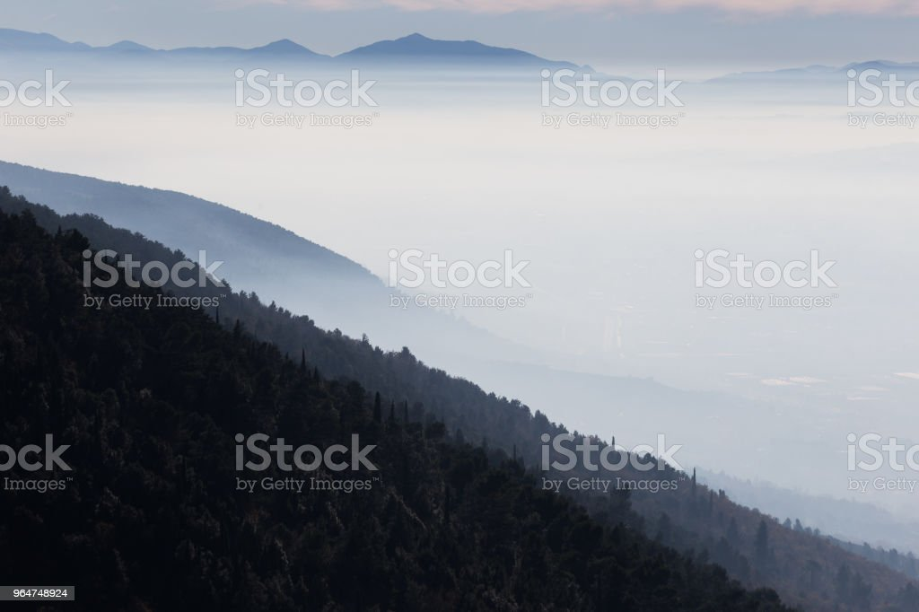 Beautiful aerial view of Umbria valley in a winter morning, with fog covering trees and houses royalty-free stock photo