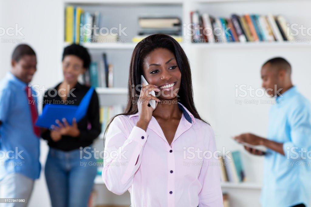 Hermosa empresaria afroamericana hablando en el teléfono con sus colegas - foto de stock