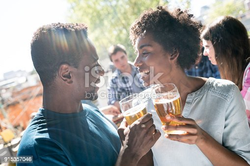 istock Beautiful african american couple on a date making a toast with beer at the bar 915357046
