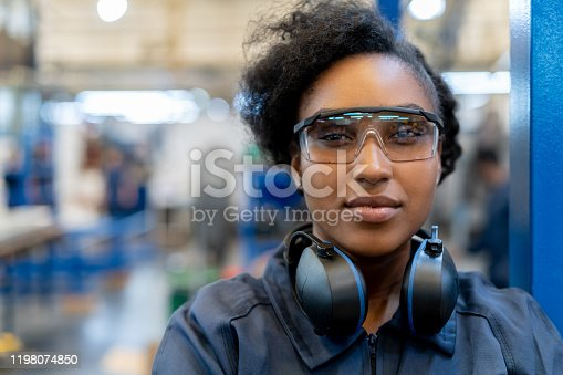 Beautiful african american engineer at a factory wearing protective workwear smiling at camera - Industrial concepts
