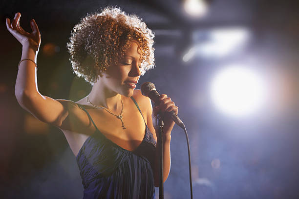 Beautiful African American female jazz singer A woman singing into the microphone on stage raising her hand above her head.  The woman is wearing a spaghetti-strapped dress.  Her hair is short and curly. singer stock pictures, royalty-free photos & images