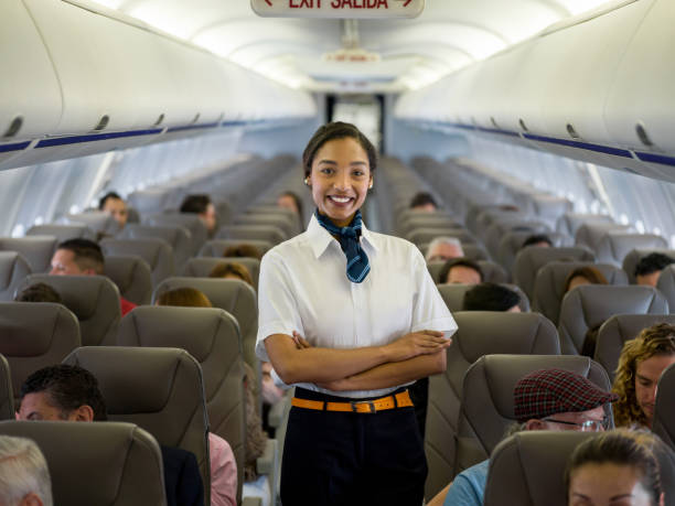 Beautiful African American flight attendant in an airplane Portrait of a beautiful African American flight attendant in an airplane looking at the camera smiling - travel concepts air stewardess stock pictures, royalty-free photos & images