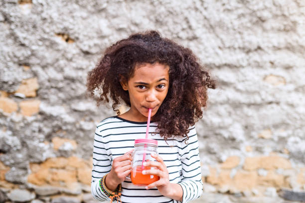 beautiful african american girl drinking juice, old concrete wall. - drinking juice stock photos and pictures