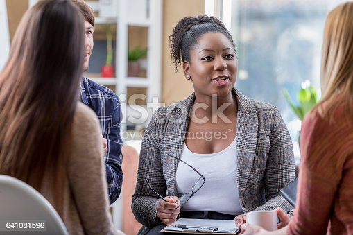 istock Beautiful African American leads group therapy session 641081596