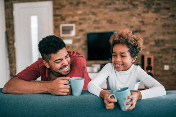 afro-americana linda garotinha e seu pai ou irmão sentado no sofá bebendo chá e se divertindo. - chá bebida quente - fotografias e filmes do acervo