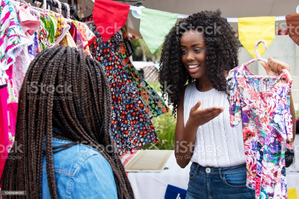 Beautiful african american market vendor presenting colorful clothes...