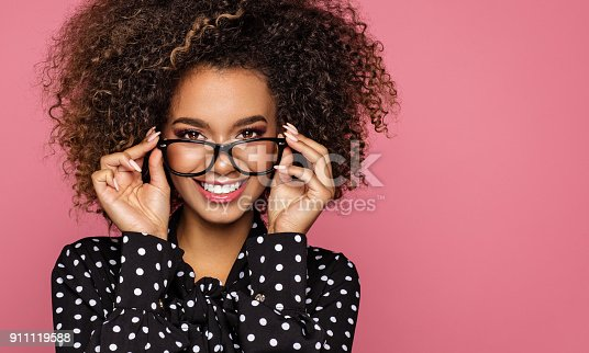 Beauty portrait of a young black healthy woman holding glasses and looking at camera