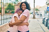 istock Beautiful african american mother and daughter smiling happy and hugging. Standing with smile on face standing at the city. 1288632132