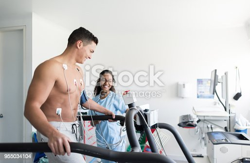 Beautiful african american nurse monitoring a cheerful male patient doing a stress test both looking very happy and smiling
