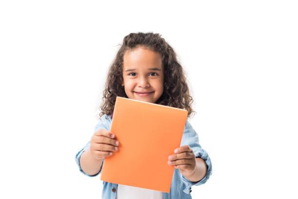 prachtige afrikaanse amerikaanse schoolmeisje holding leerboek en glimlachend op camera geïsoleerd op wit - a little girl reading a book stockfoto's en -beelden