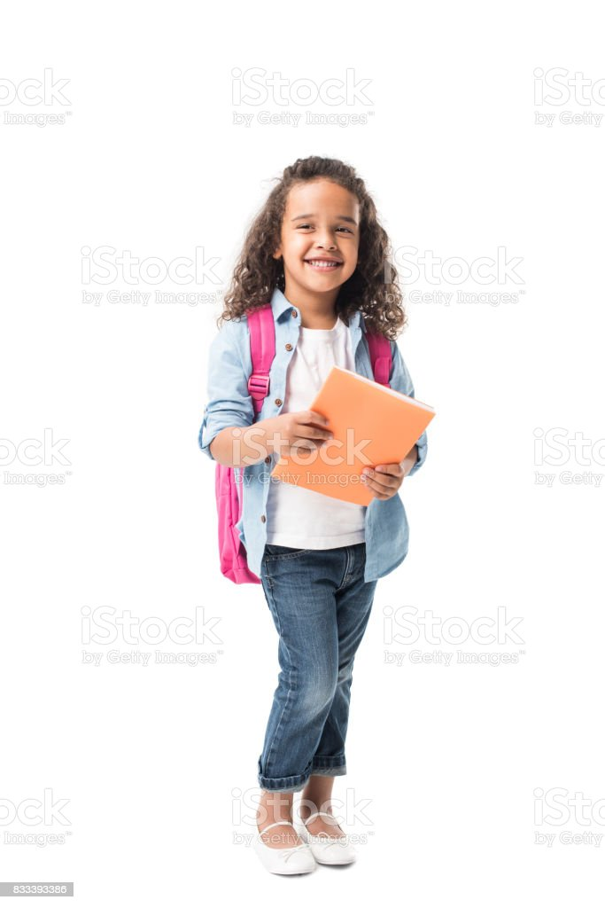 beautiful african american schoolgirl holding textbook and smiling at camera isolated on white stock photo