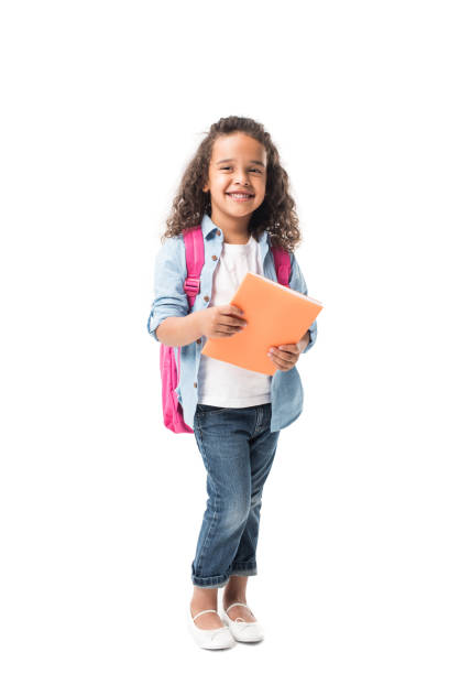 beautiful african american schoolgirl holding textbook and smiling at camera isolated on white - one girl only stock pictures, royalty-free photos & images