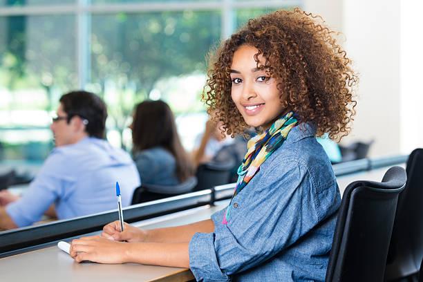 bellissimo afro-americana teen ragazza prendendo appunti in classe college - professore di scuola superiore foto e immagini stock
