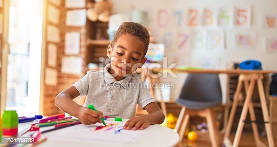 Beautiful african american toddler drawing using paper and marker pen at kindergarten