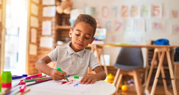 Beautiful african american toddler drawing using paper and marker pen at kindergarten stock photo