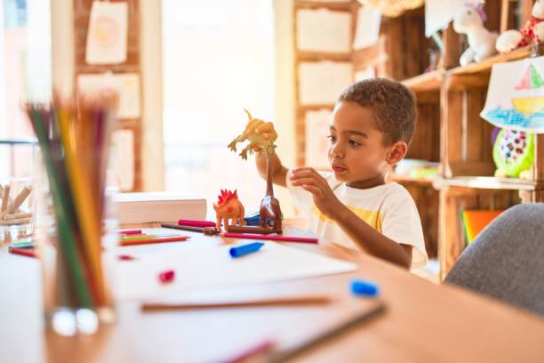 Beautiful african american toddler playing with dinosaurs toy on desk at kindergarten stock photo