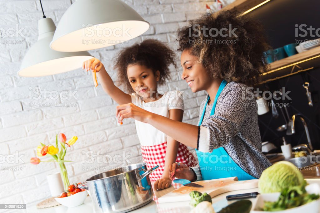 Beautiful African American woman and her daughter cooking in the kitchen stock photo